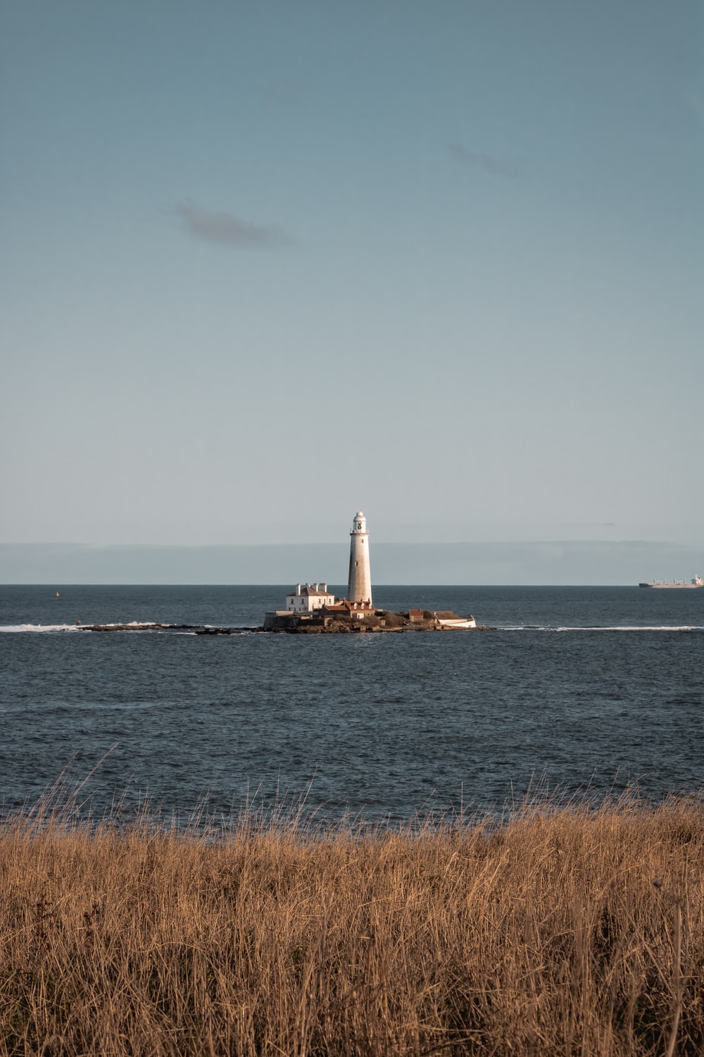 white and brown lighthouse on sea under white sky during daytime