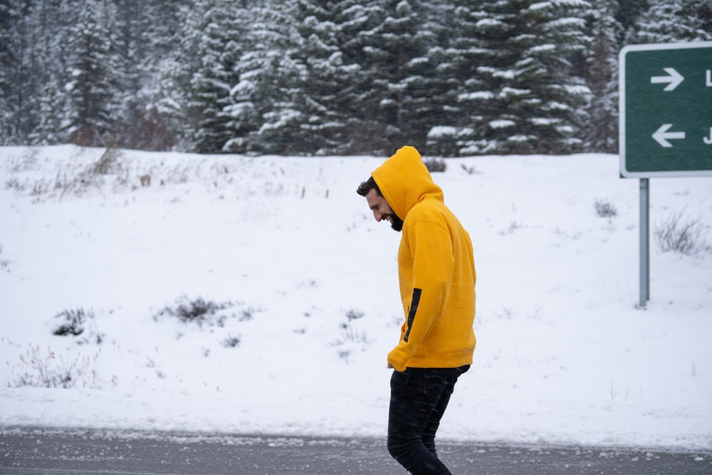 person in yellow hoodie standing on snow covered ground during daytime