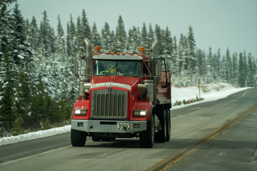 red and white truck on road during daytime