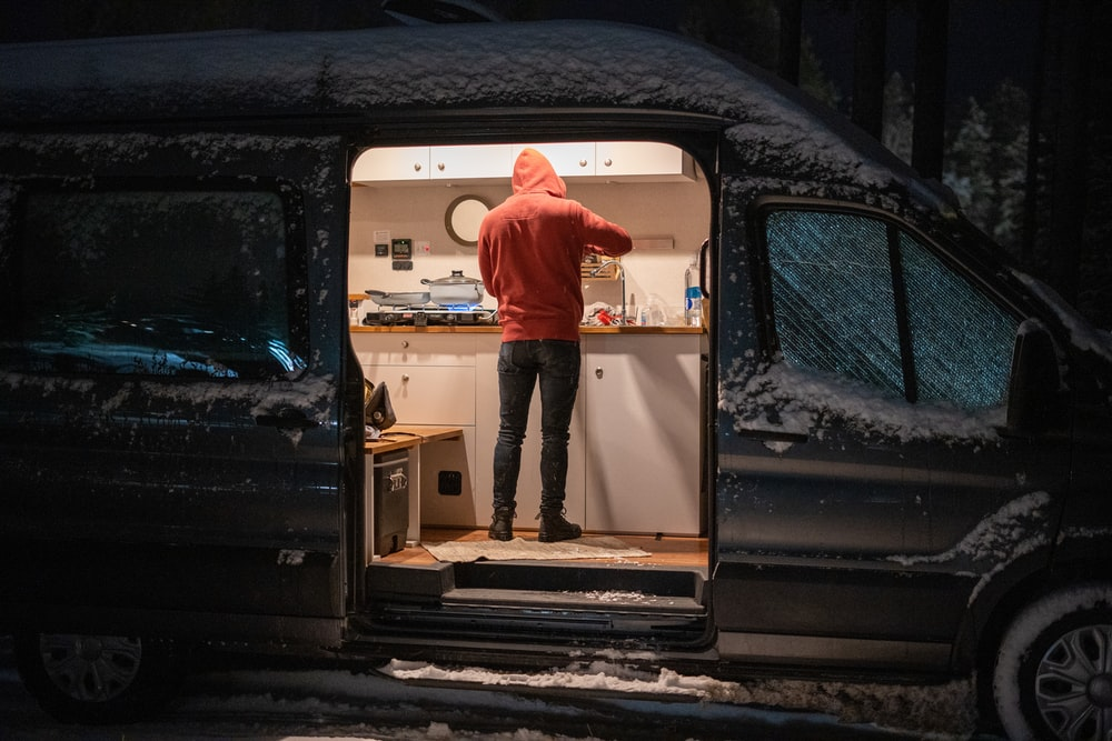 man in red hoodie standing in front of white and black car door