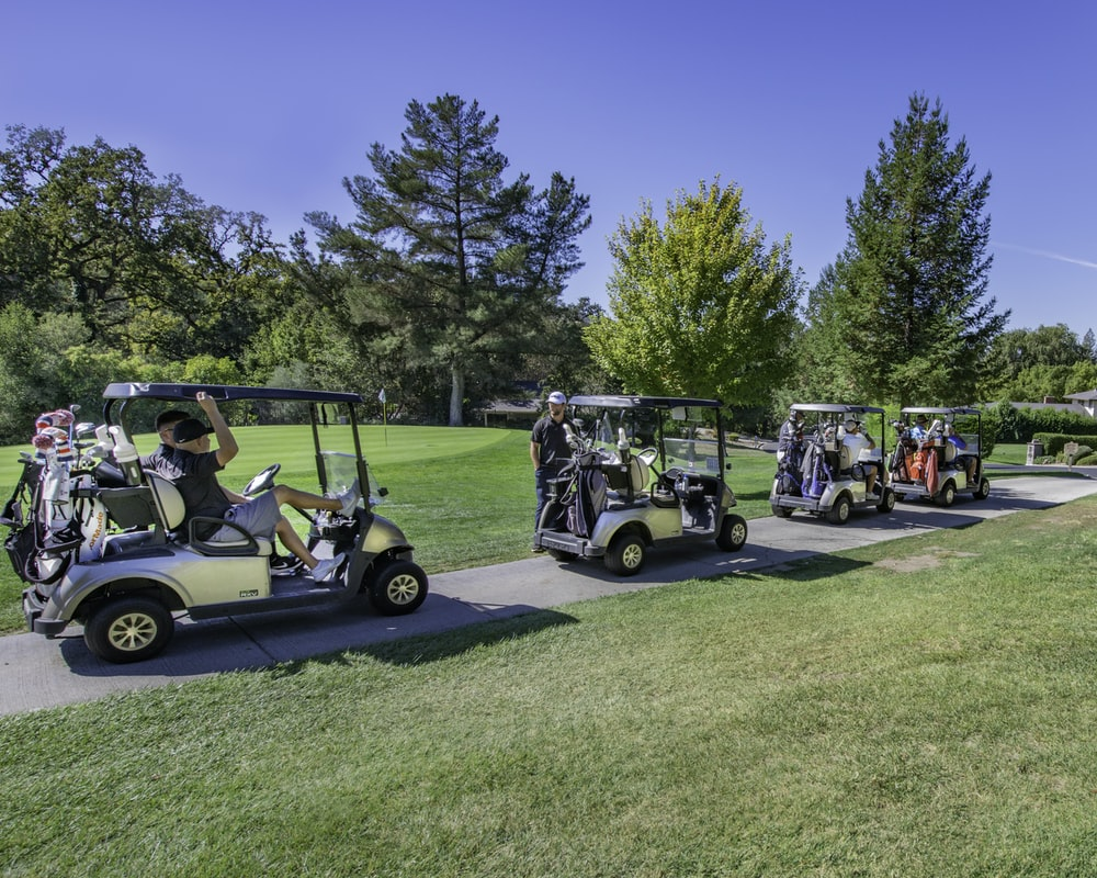 white golf cart on green grass field during daytime