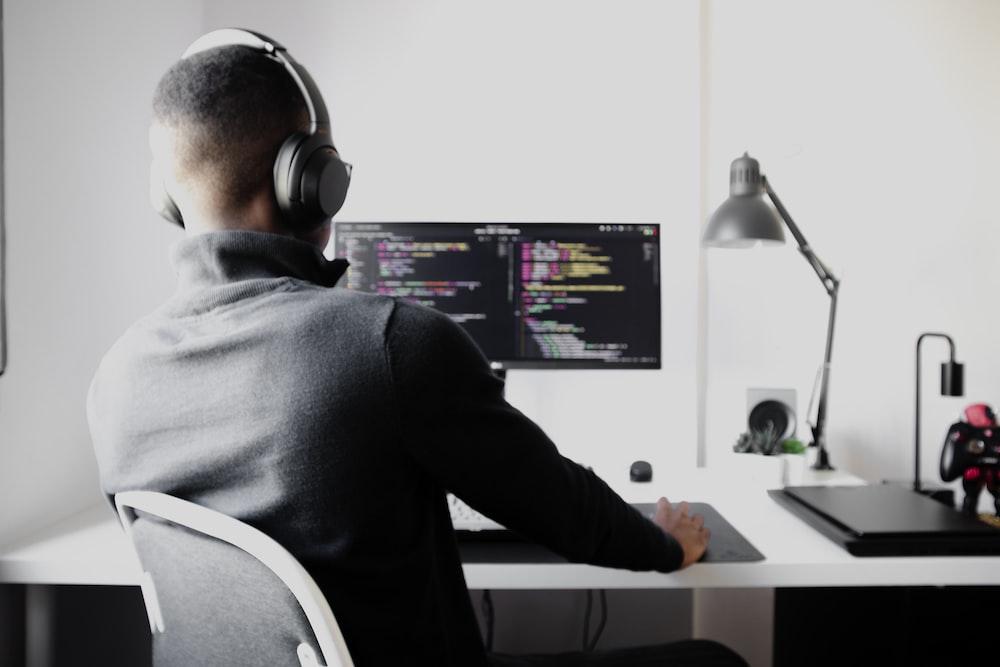 man in black long sleeve shirt wearing black headphones sitting on chair