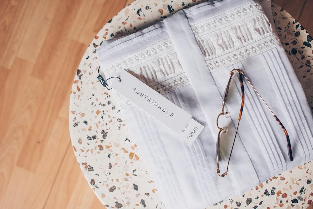 silver framed eyeglasses on white and blue floral textile