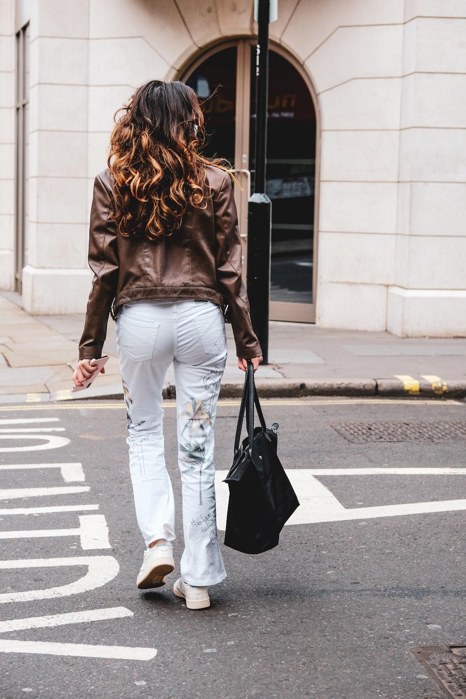 woman in black long sleeve shirt and white pants walking on pedestrian lane