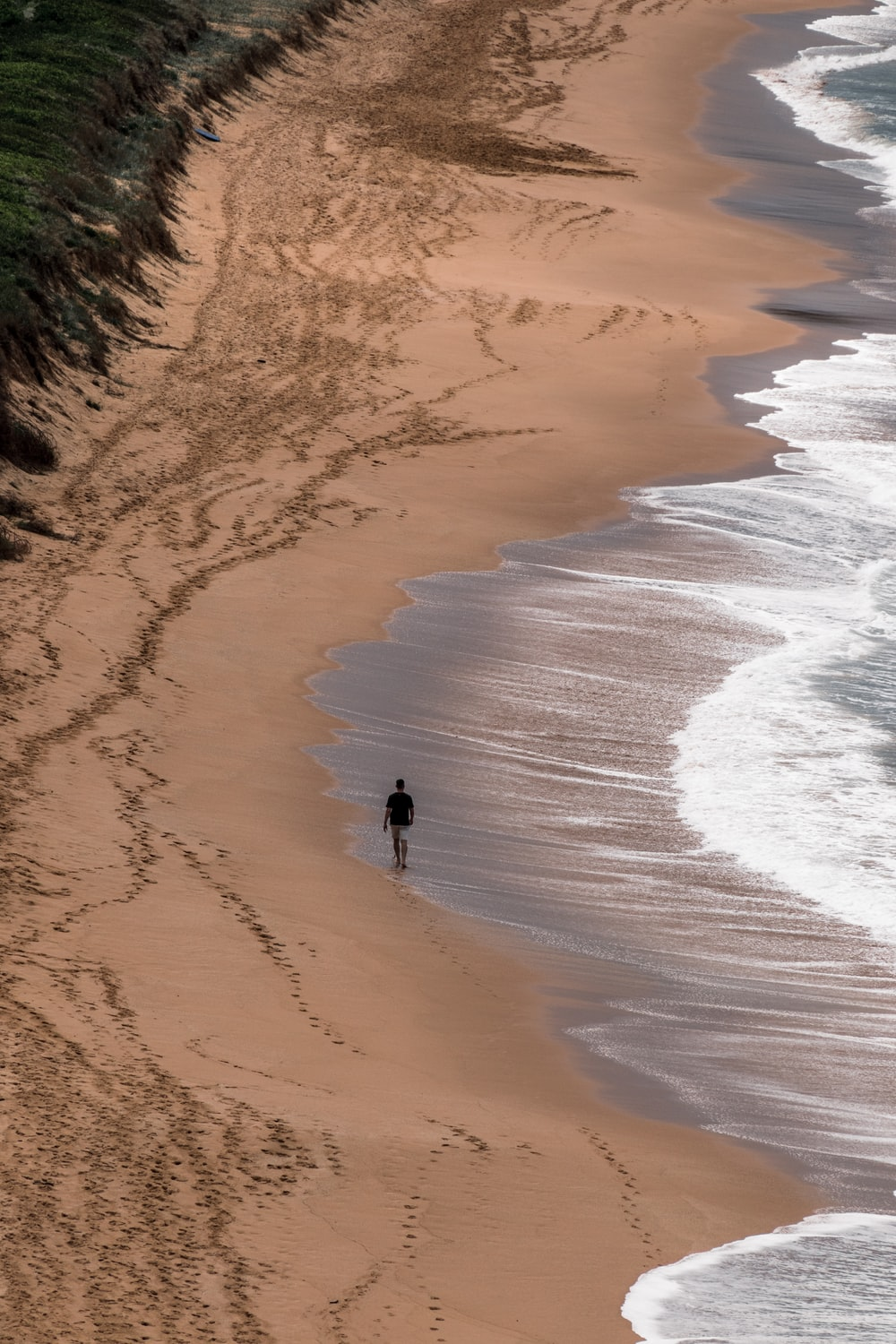 man in black shirt walking on beach during daytime