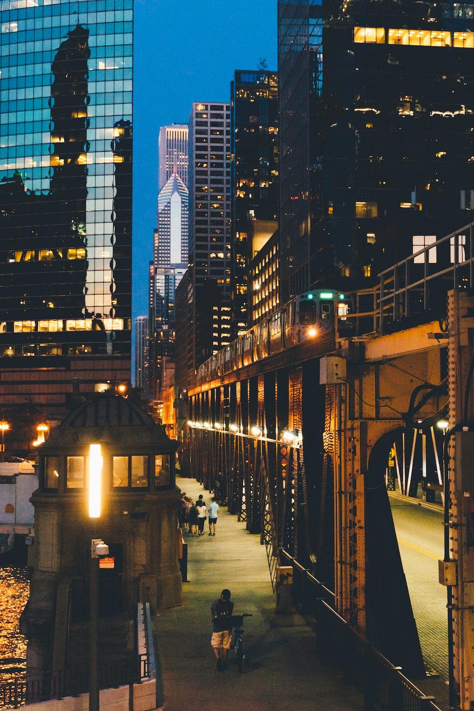 people walking on sidewalk near buildings during night time