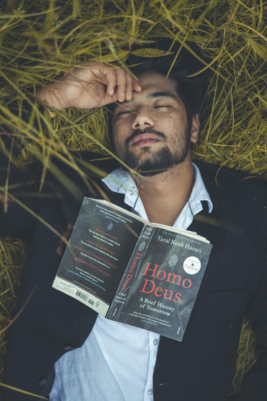 man in black suit jacket holding black book