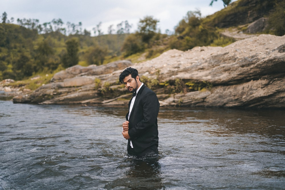 man in black suit standing on river during daytime