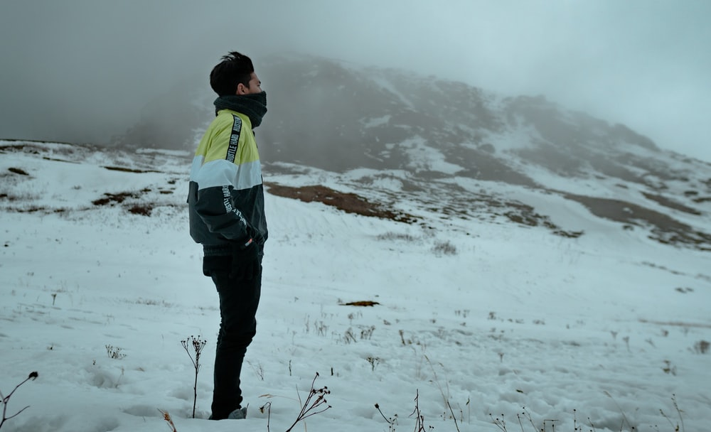 man in green and black jacket and black pants standing on snow covered ground