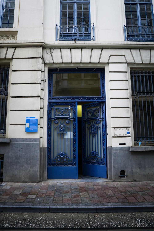blue wooden door on white concrete building