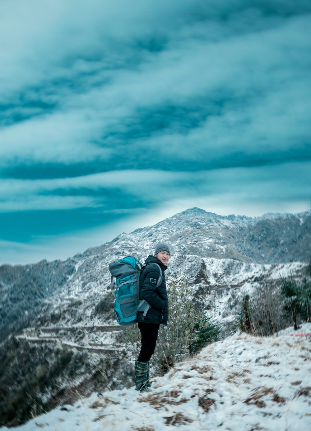 man in black jacket and blue backpack standing on snow covered ground during daytime