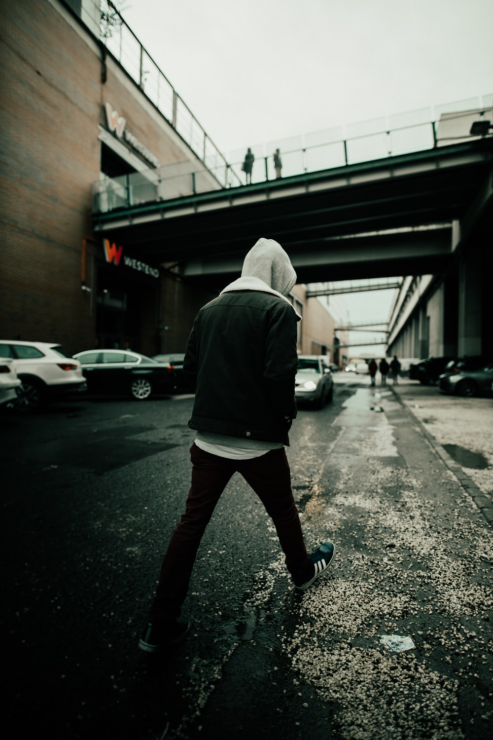person in gray hoodie and black pants walking on sidewalk during daytime
