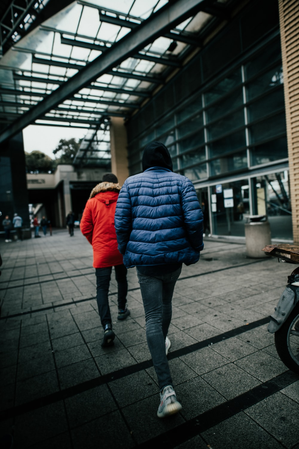 woman in red bubble jacket and blue denim jeans walking on sidewalk during daytime