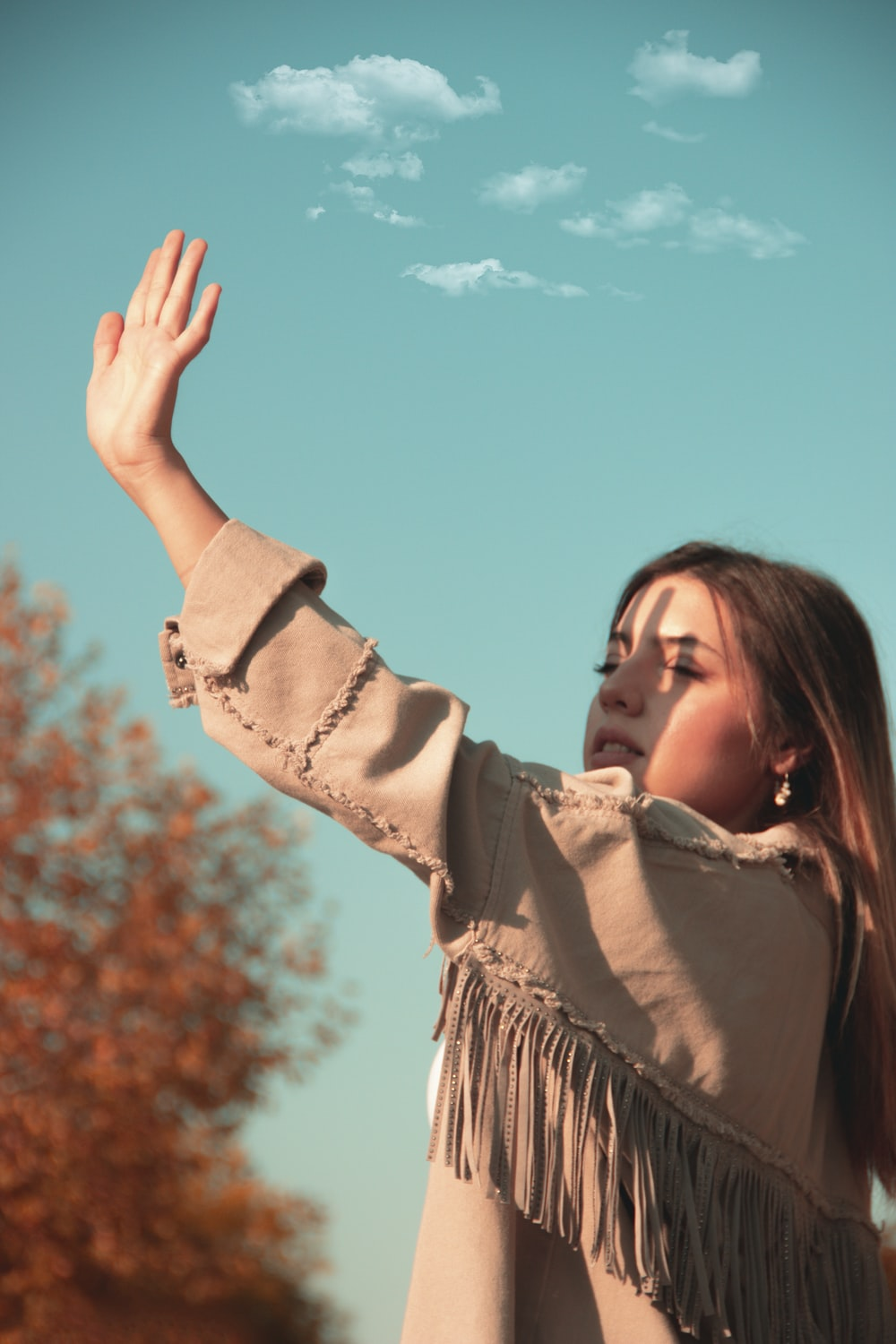 woman in brown long sleeve shirt raising her right hand