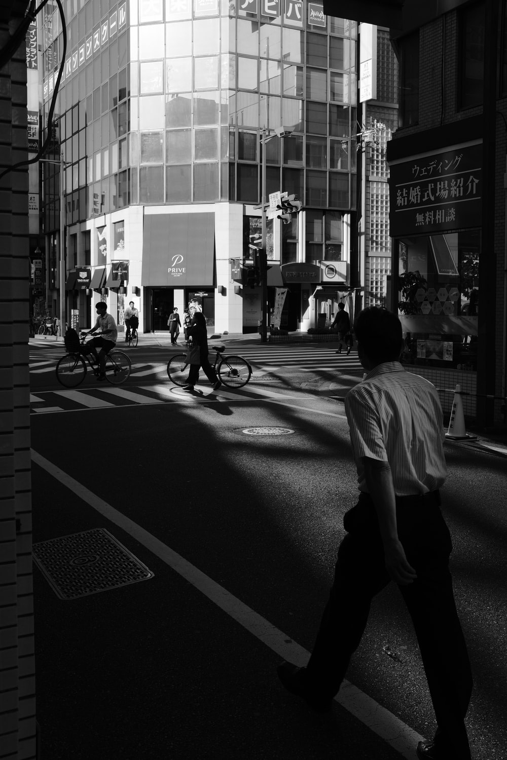 grayscale photo of man in white t-shirt and black pants walking on street