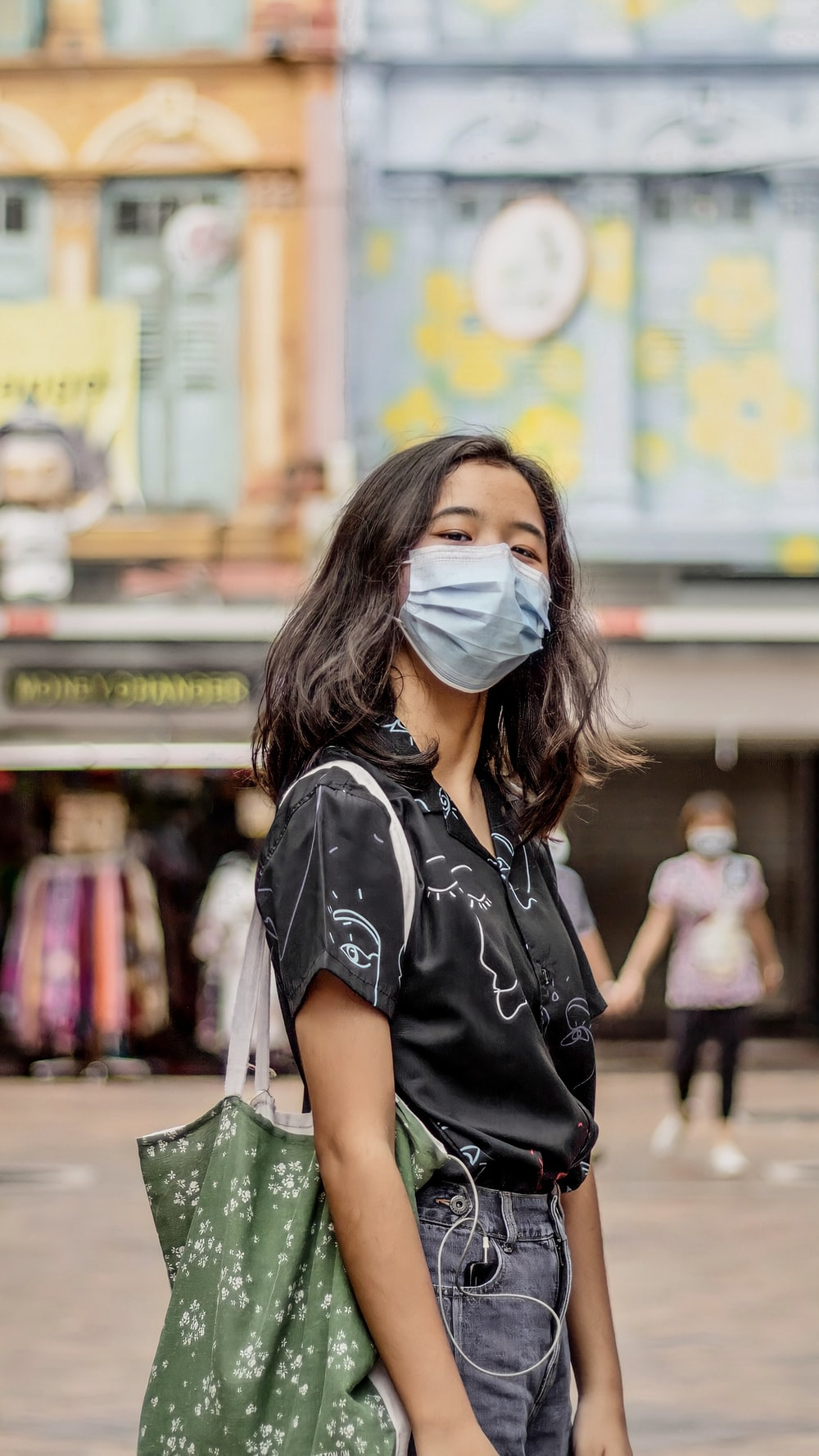 woman in black and white shirt wearing white mask