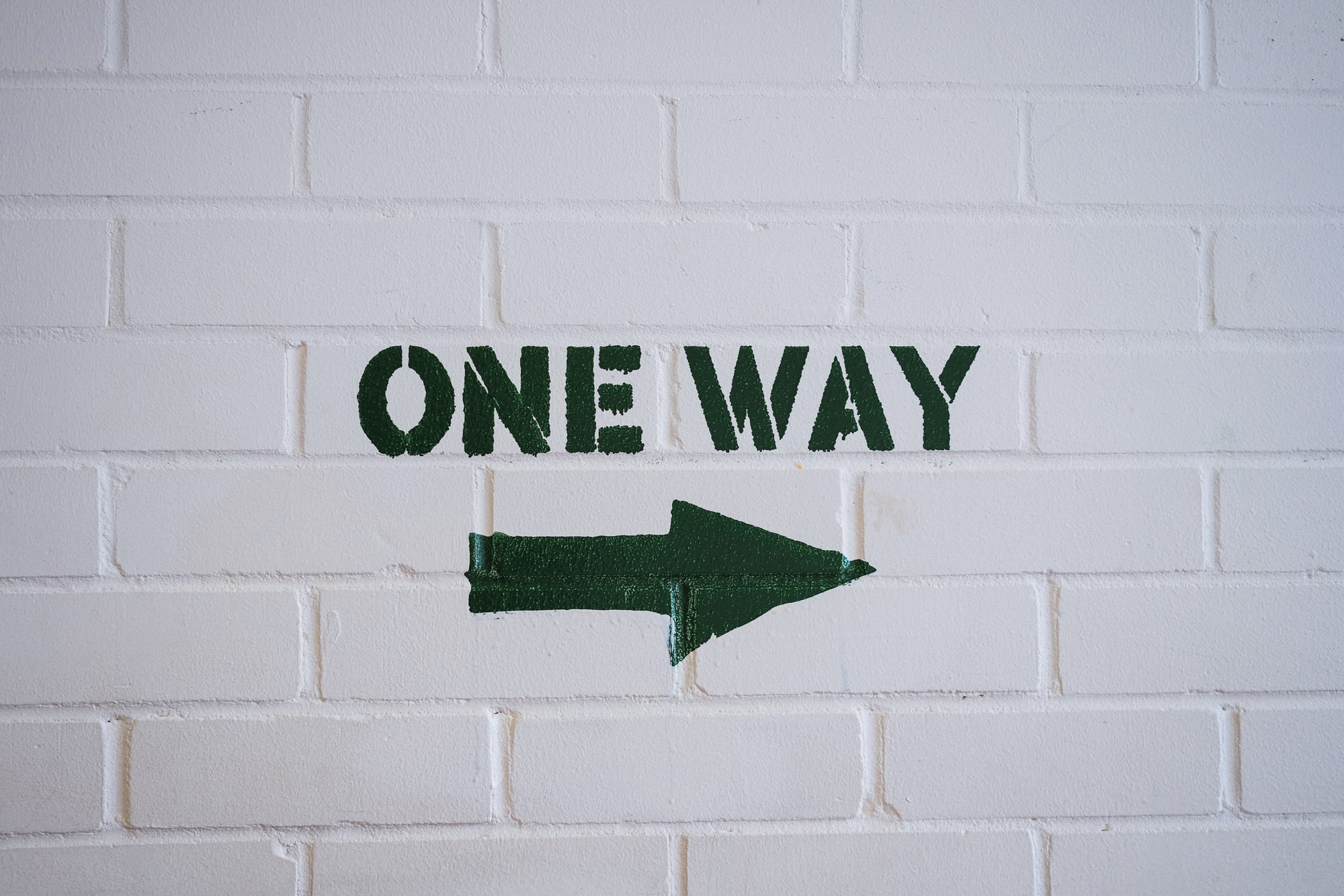 One Way Sign on a white brick wall