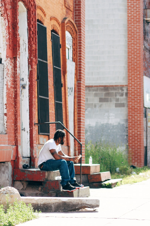 man in white t-shirt sitting on brown wooden bench during daytime