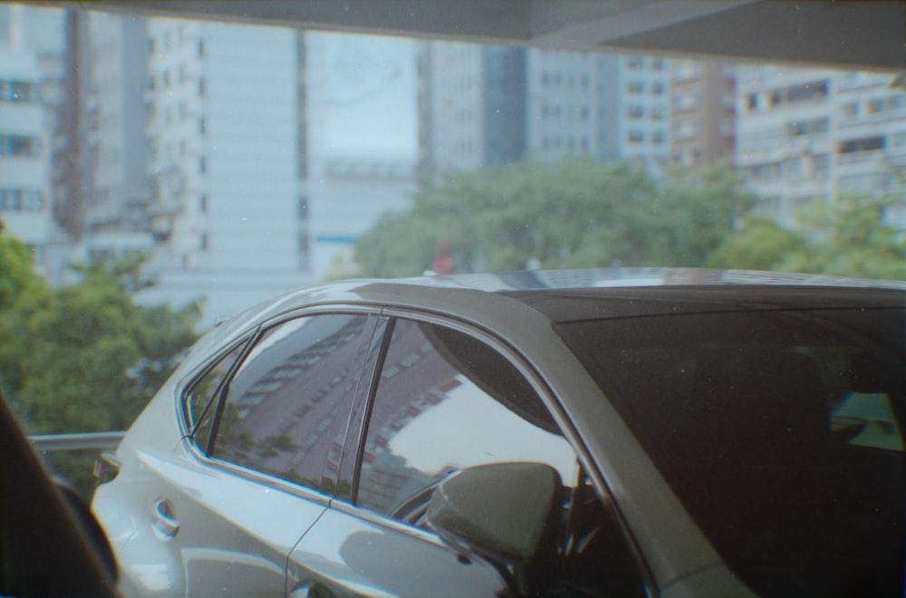 white sedan parked near white building during daytime