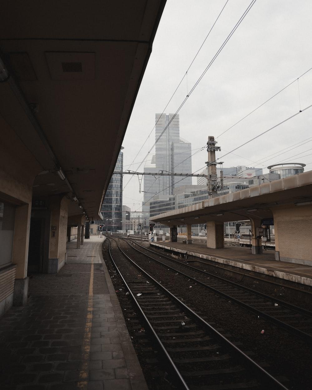 train rail under white sky during daytime