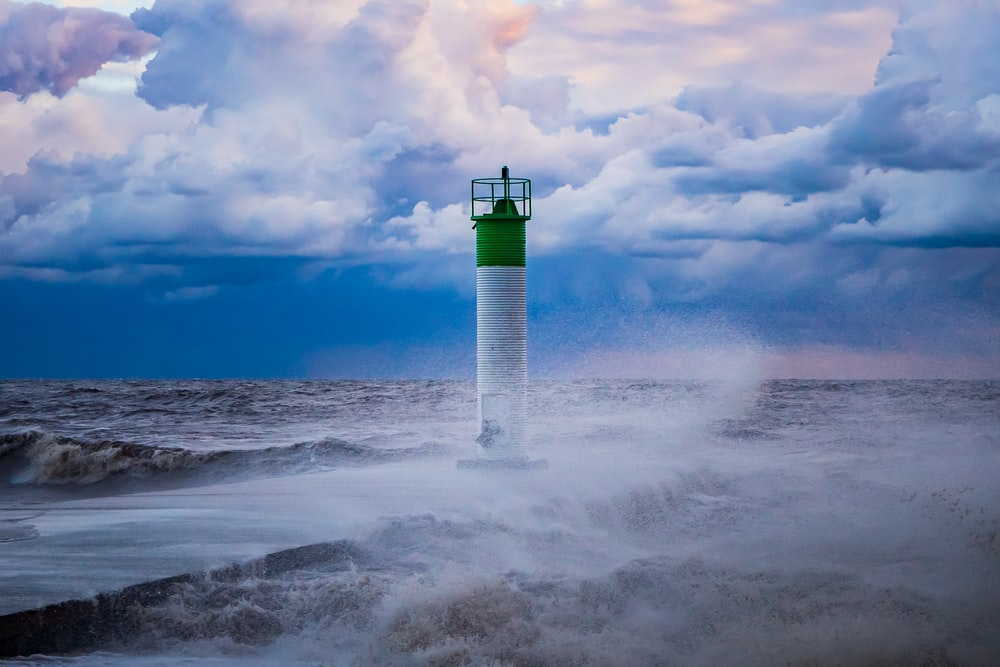 white and green lighthouse on white clouds during daytime
