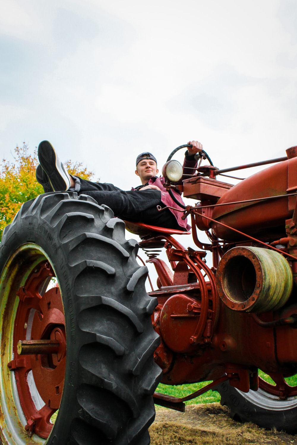 man in black jacket riding red tractor