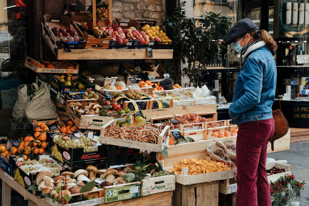 man in blue jacket standing in front of fruit stand