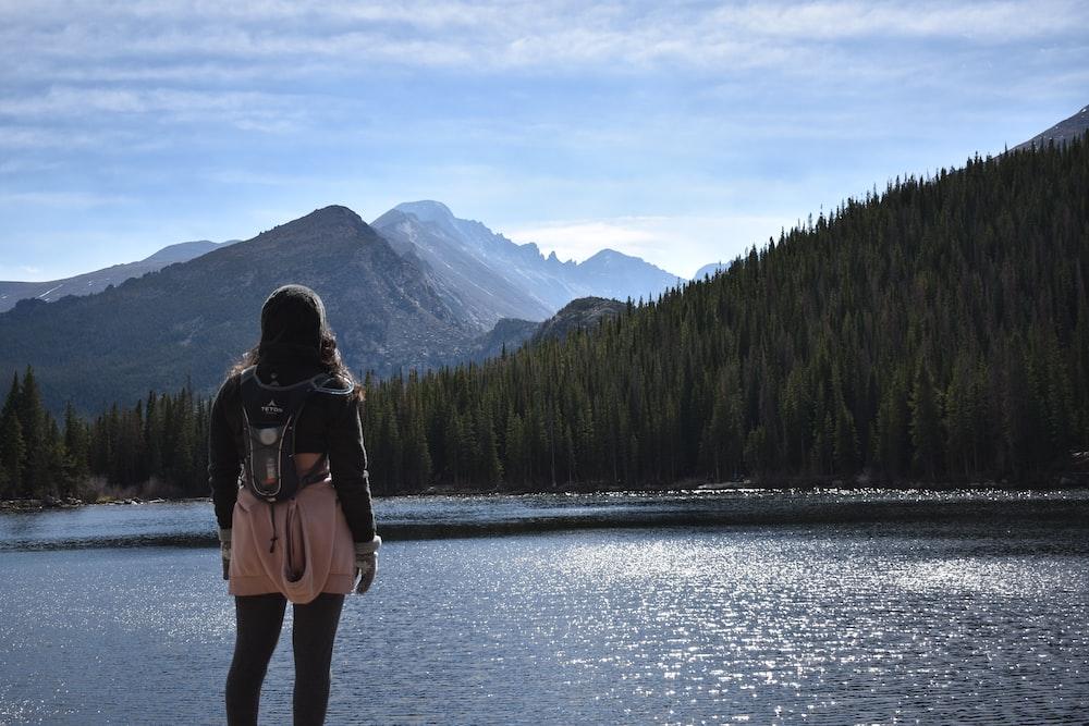 woman in black jacket standing on lake during daytime