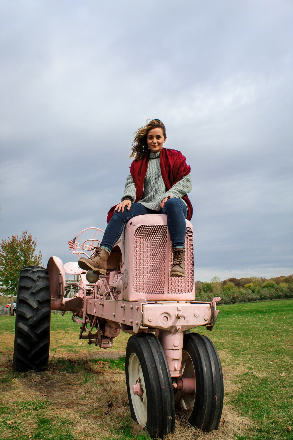 woman in red long sleeve shirt riding red tractor on green grass field during daytime