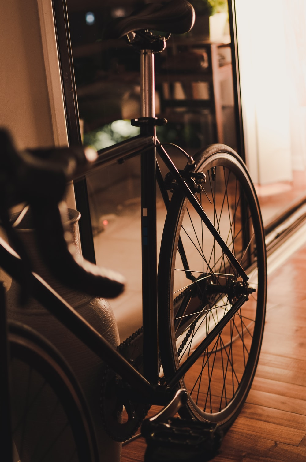 grayscale photo of bicycle near window