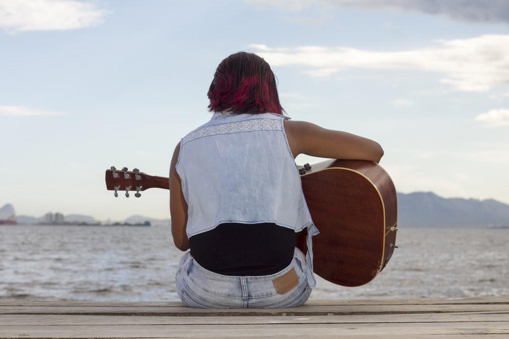 woman in white shirt and black shorts playing brown acoustic guitar