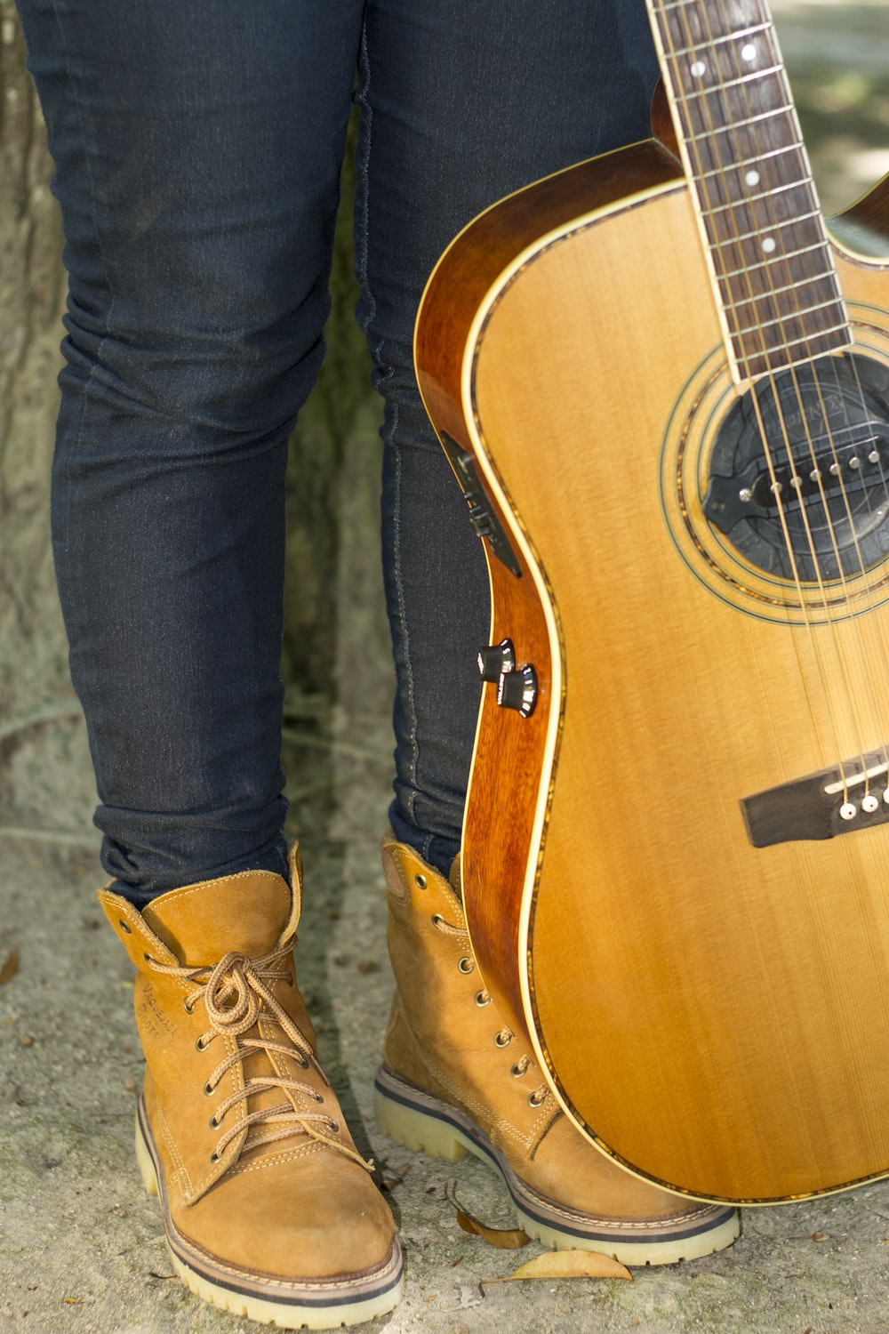person in blue denim jeans and brown leather boots standing beside brown acoustic guitar