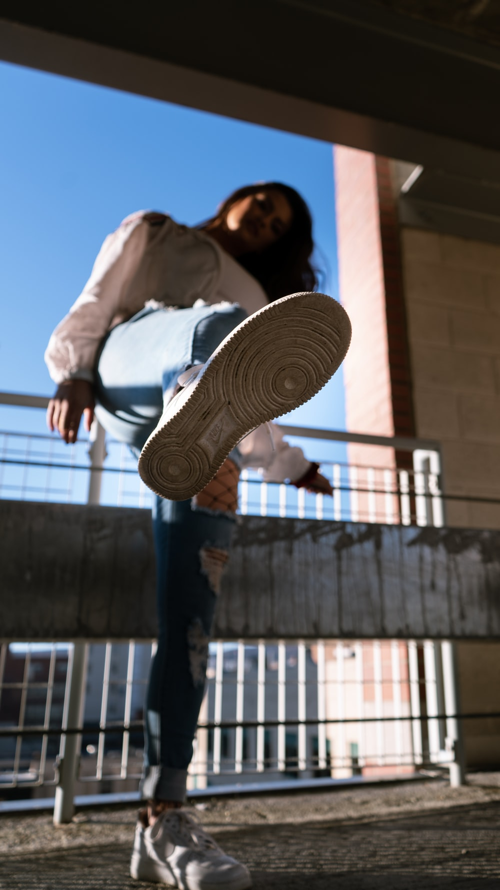 woman in white long sleeve shirt and blue denim jeans standing on brown concrete building during
