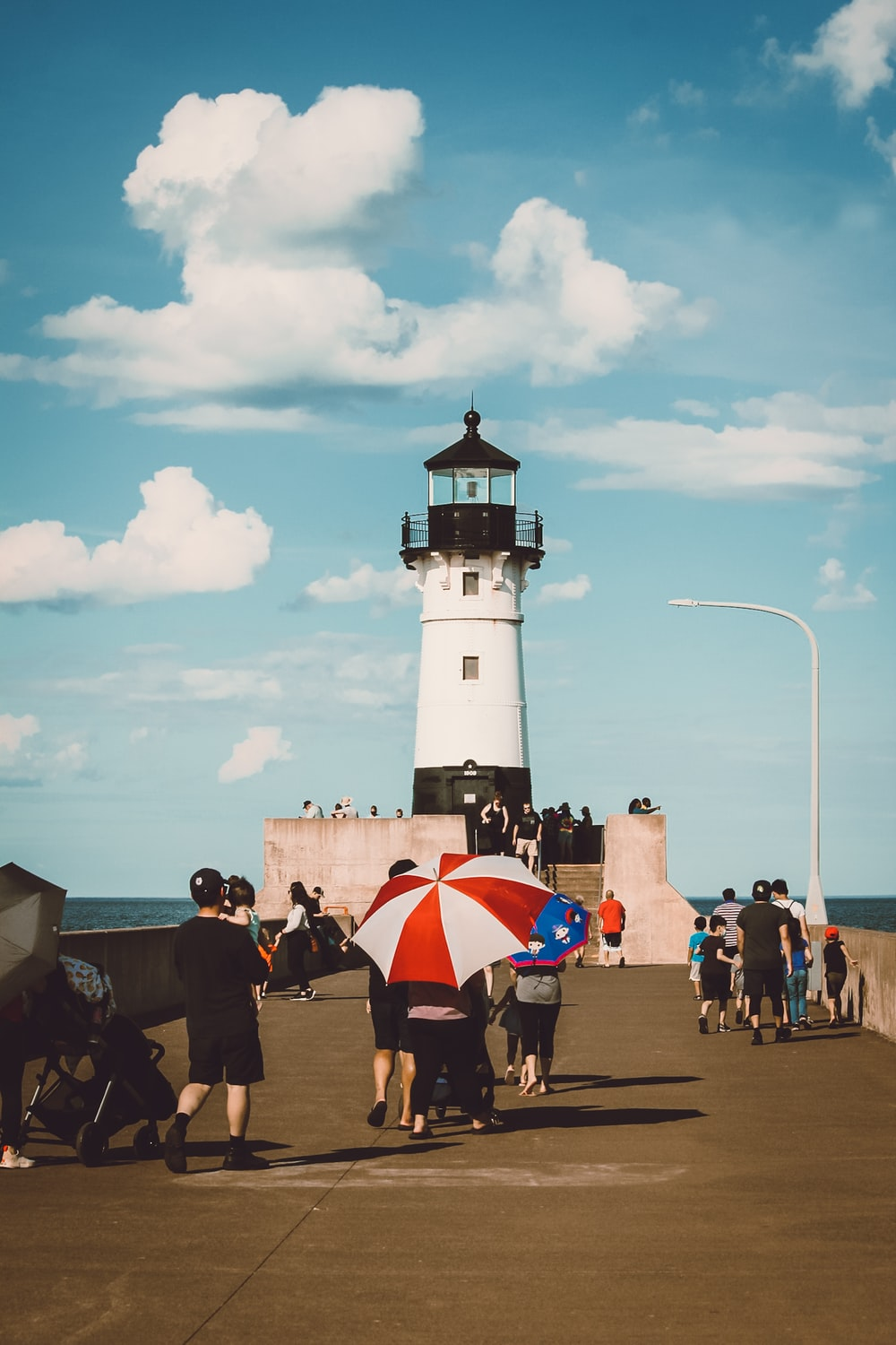 people walking near white and black lighthouse under blue and white cloudy sky during daytime