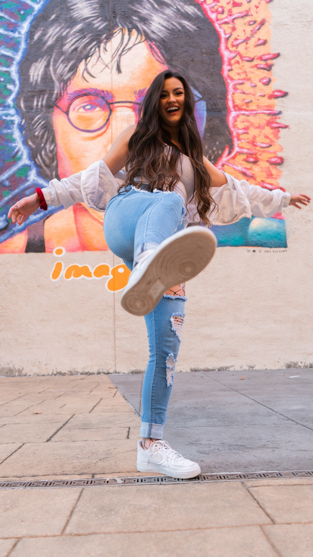 woman in blue denim jeans and gray shirt sitting on concrete wall during daytime