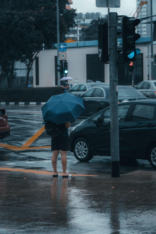 woman in black jacket and blue denim shorts walking on pedestrian lane during daytime