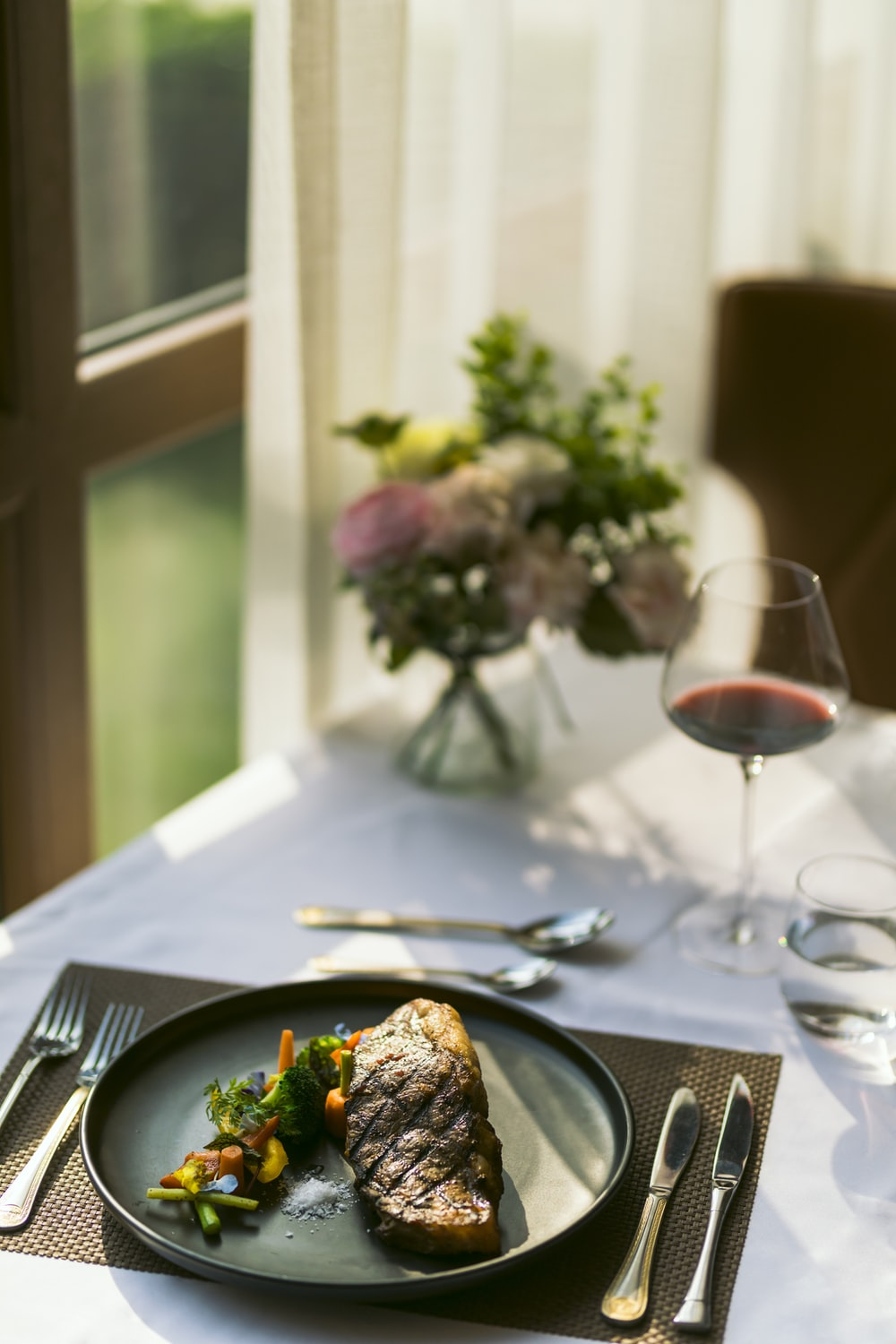 cooked food on black ceramic plate beside wine glass on table