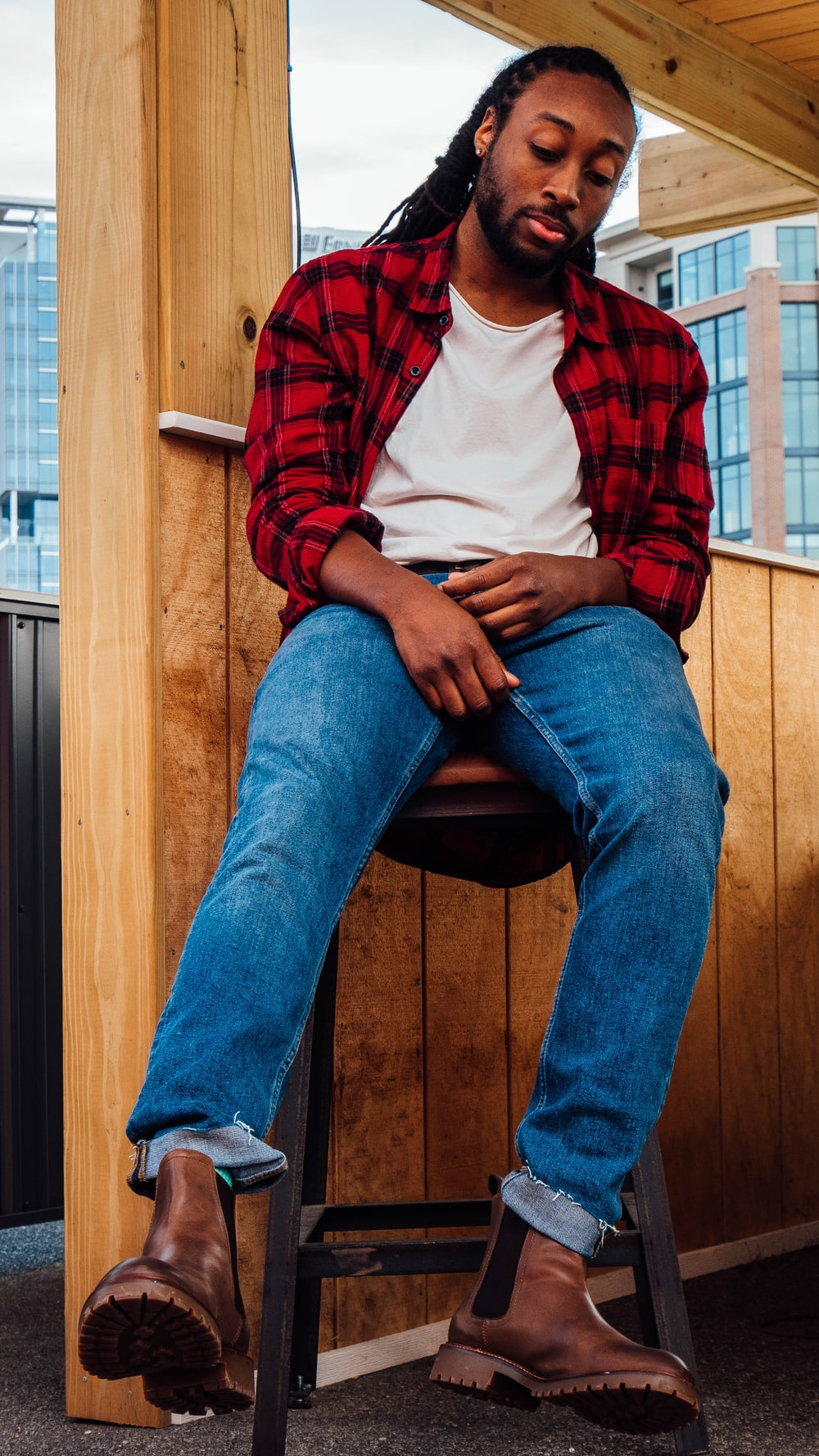 man in red and white plaid dress shirt and blue denim jeans sitting on brown wooden