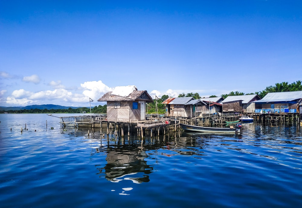 white and brown wooden houses on body of water under blue sky during daytime