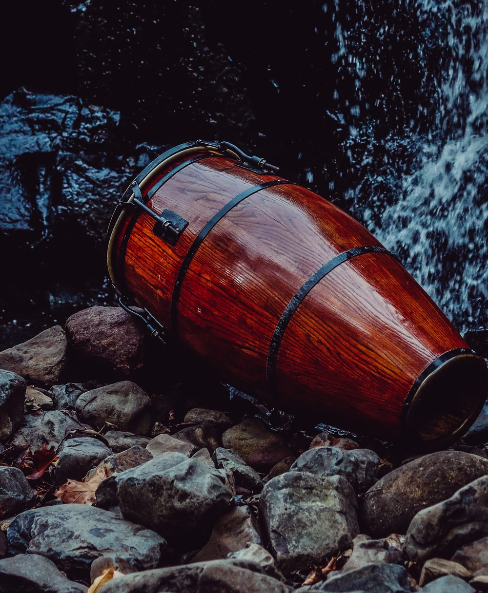 brown wooden barrel on rocky shore