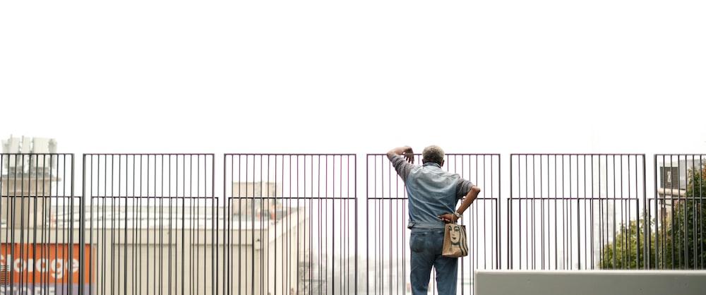 man in blue denim jacket and brown pants standing beside black metal fence