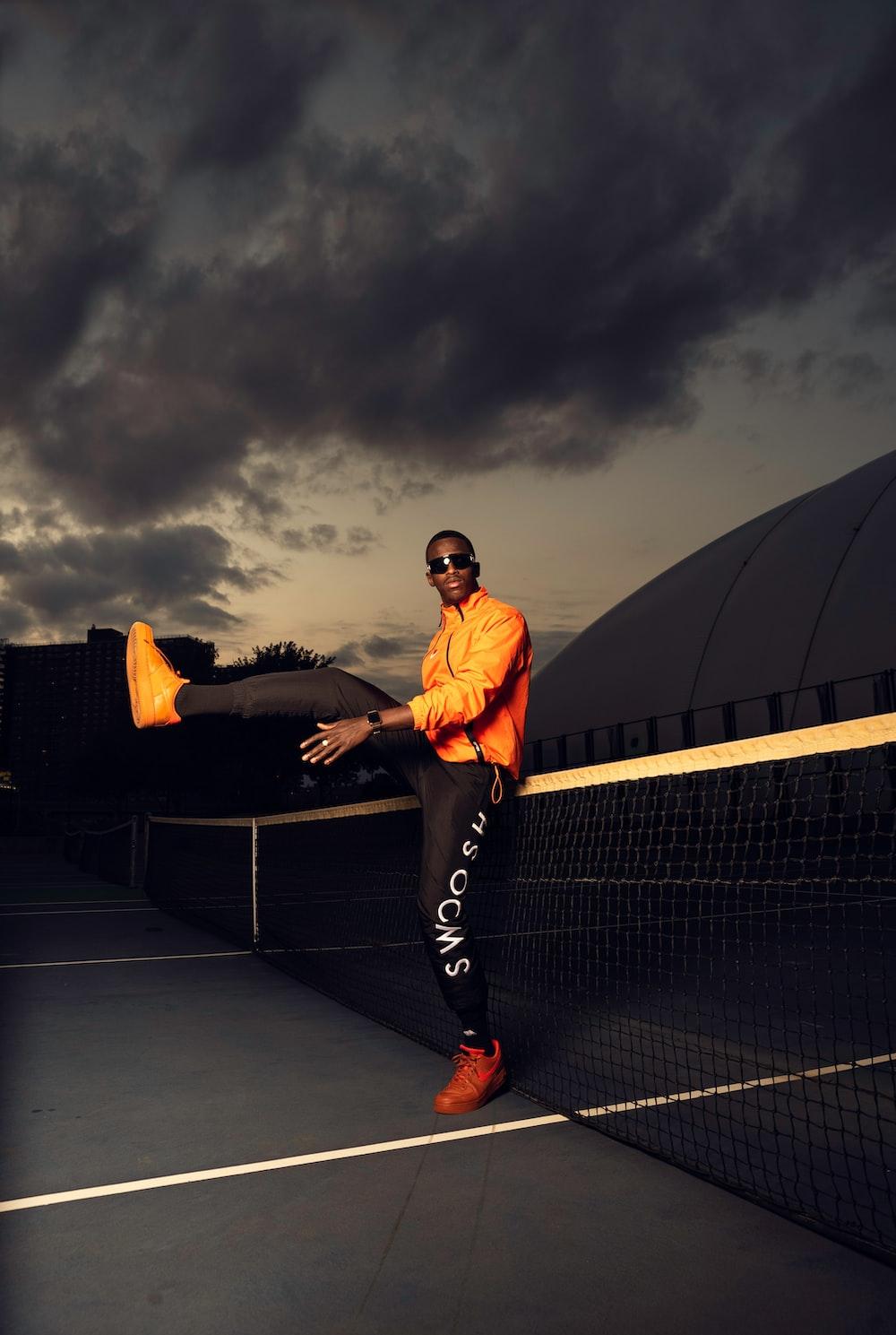 man in orange shirt and black pants standing on black bench