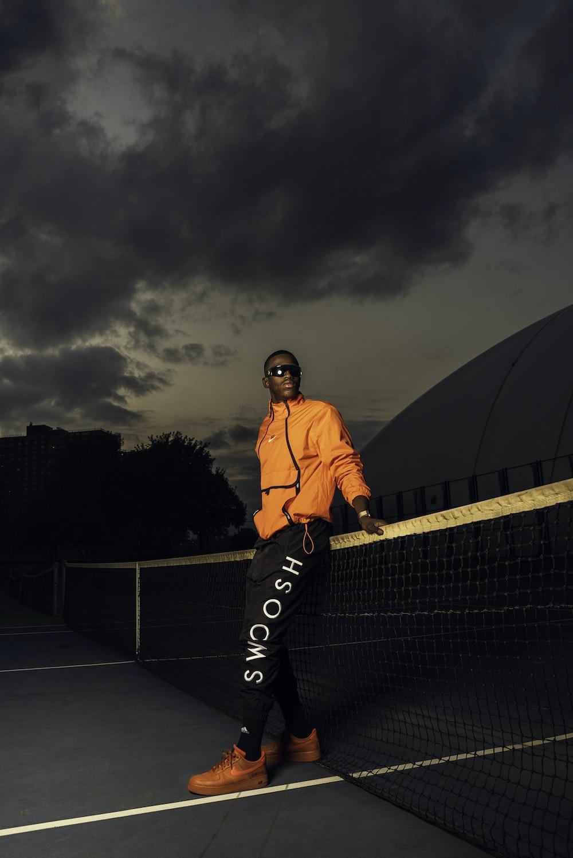 man in orange jacket standing on black metal fence during night time