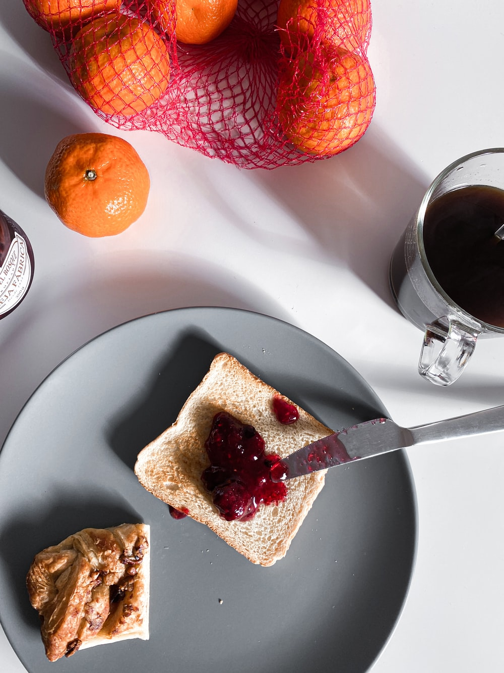 sliced bread on white ceramic plate beside clear drinking glass