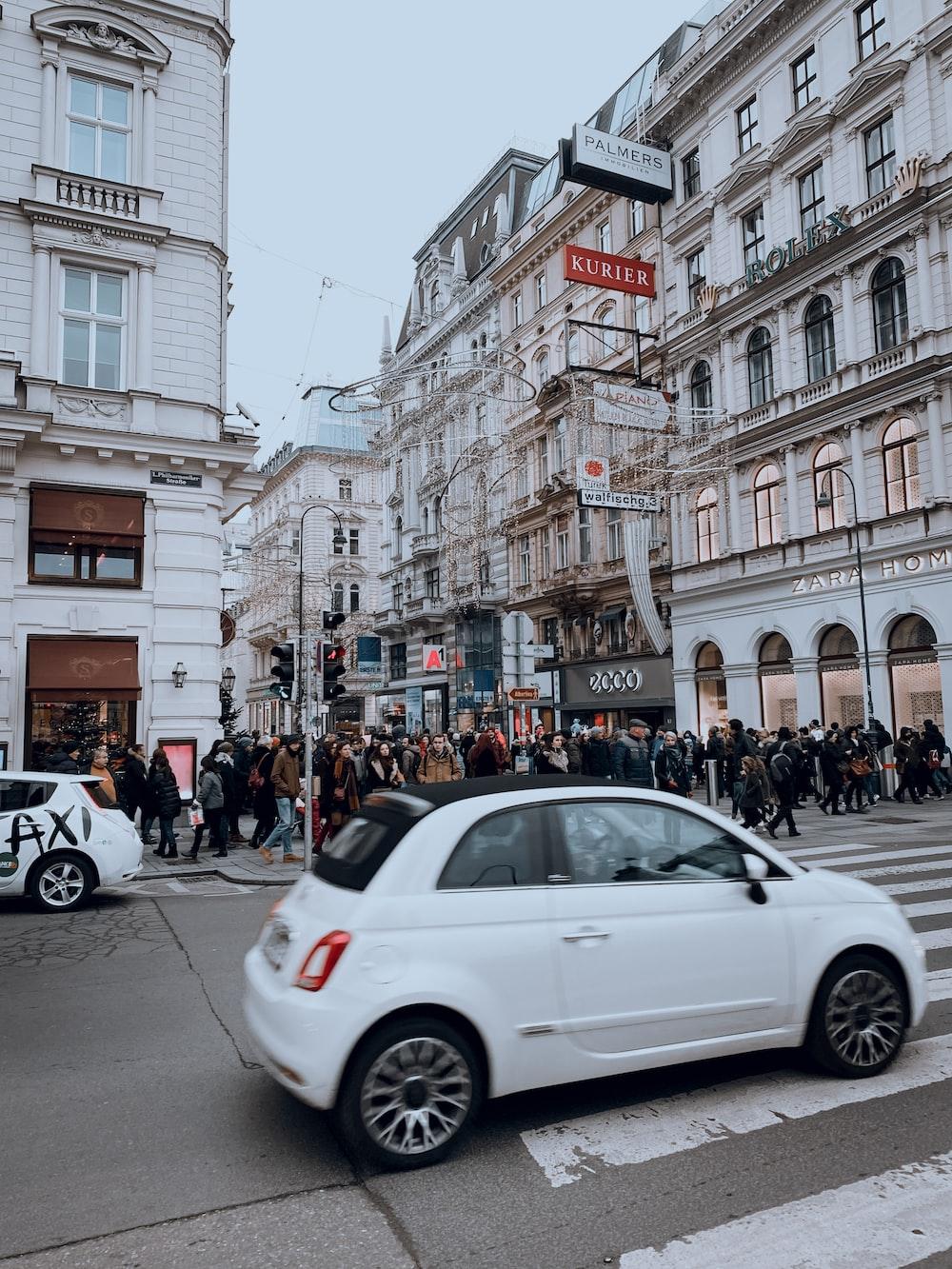 white sedan on road near people walking on sidewalk during daytime