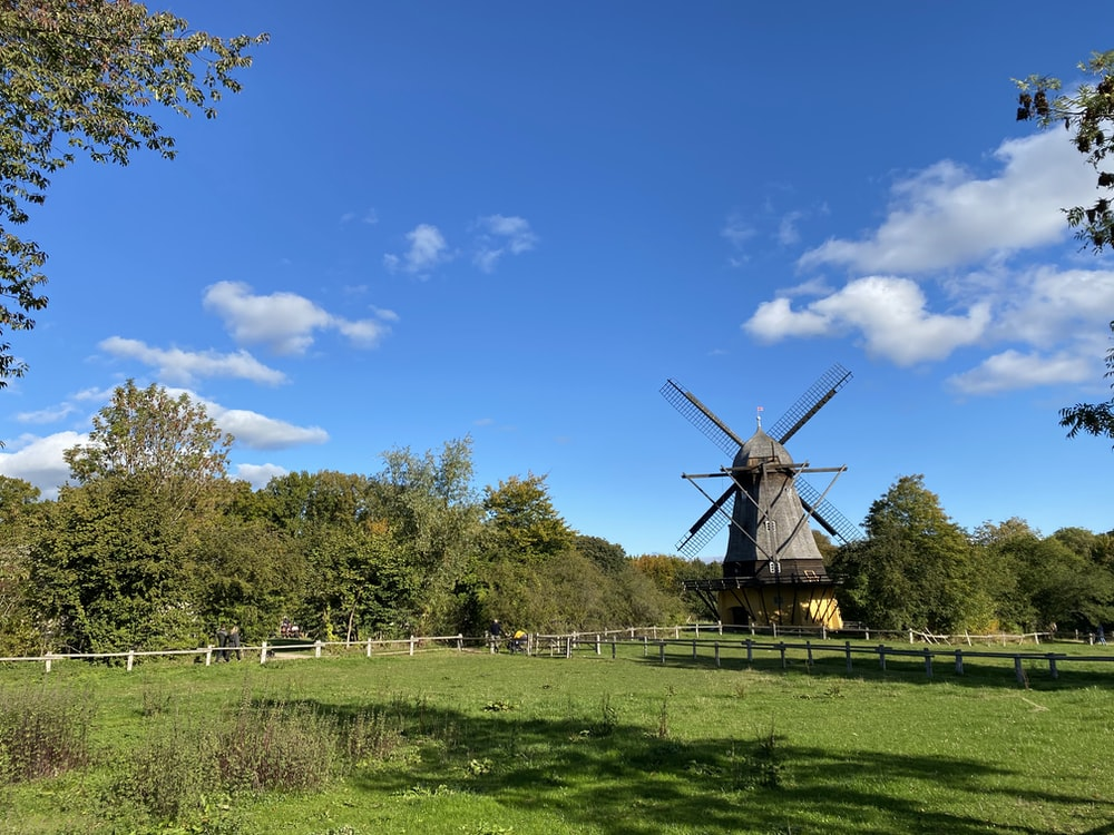 brown windmill on green grass field under blue sky during daytime