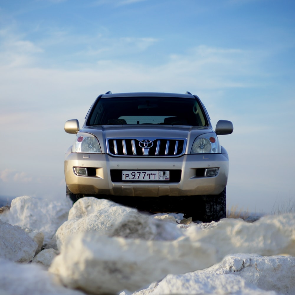 white nissan suv on snow covered ground under blue sky during daytime