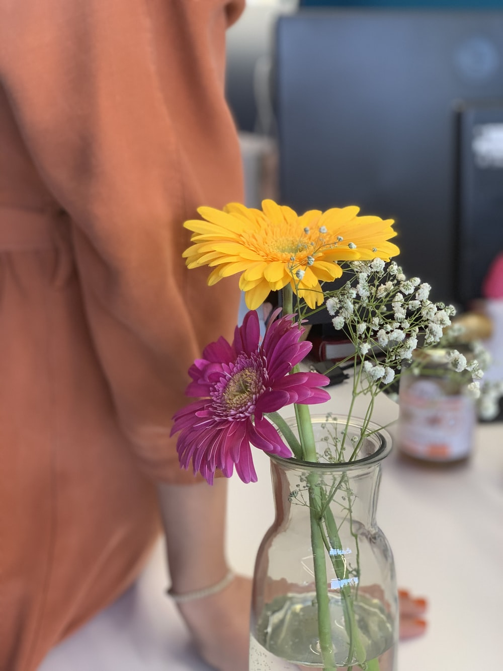 yellow and purple flowers in clear glass vase