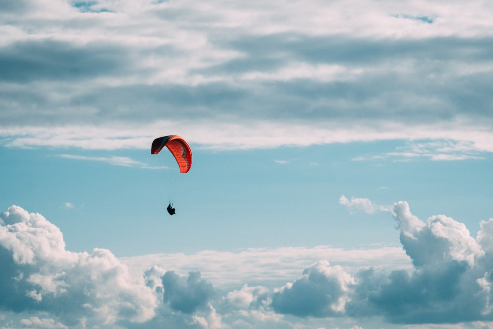 person in red parachute under white clouds during daytime