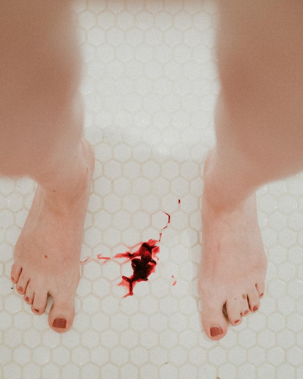 person standing on white ceramic floor tiles